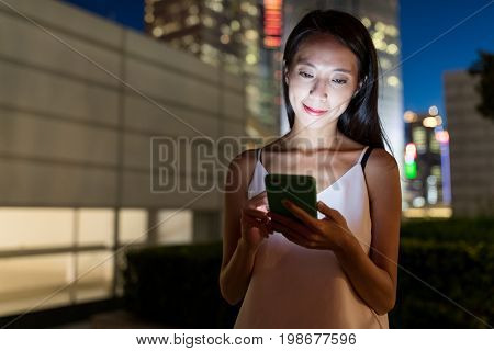 Woman watching on cellphone in the city at night
