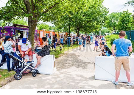 Washington DC USA - July 3 2017: People eating fast food on sidewalk and walking from food trucks on street by National Mall on Independence Avenue