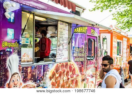 Washington DC USA - July 3 2017: Food trucks on street by National Mall with Manhattan Pizza storefront on Independence Avenue and people buying
