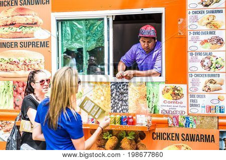 Washington DC USA - July 3 2017: Food trucks on street by National Mall with Middle Eastern Food storefront on Independence Avenue and people buying