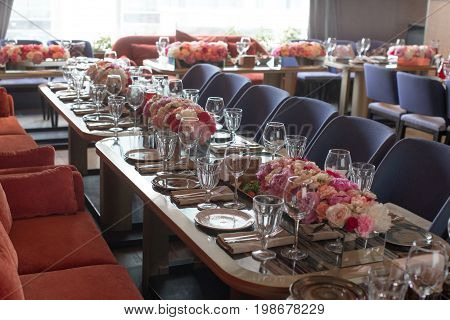 Table served with flowers and dishware for event in modern restaurant.