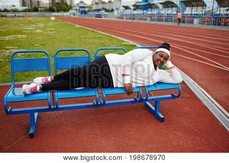 Plump African woman lying on bench and relaxing after exercising at track and field stadium, feeling happy and confident