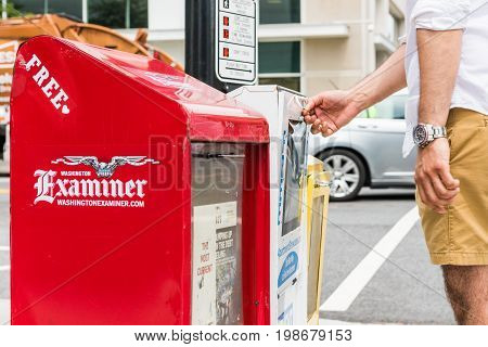 Washington DC USA - July 3 2017: Newspaper kiosks vending machines on National Mall with person opening National Examiner