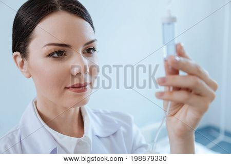 Hospital worker. Pleasant nice professional nurse smiling and looking at the IV drip bottle while setting up an IV line