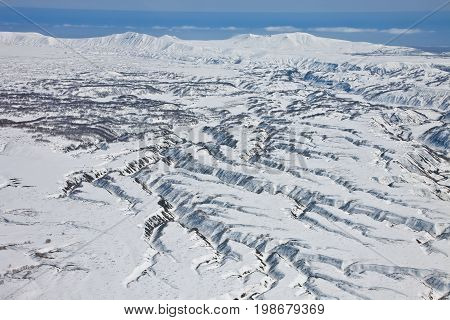Mountainous terrain ravines erosion of the surface around the volcano on the Kamchatka Peninsula. Neighborhood Karymsky volcano after a fresh snowfall in the spring from a helicopter. Russia.