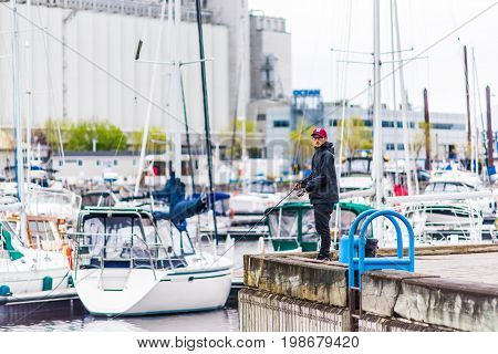 Quebec City Canada - May 30 2017: Fisherman man fishing in port harbor marina area of town with many boats