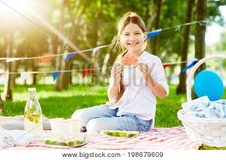 Cute girl eating water-melon in park during picnic in summer