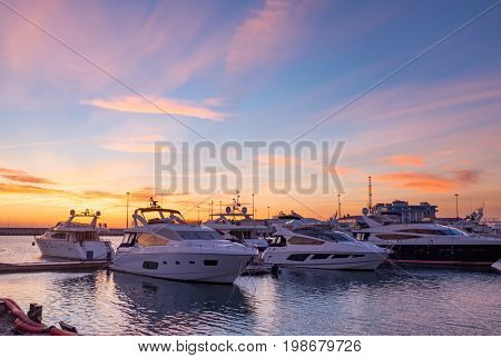 Beautiful Golden Hour Sunset In A Marina With Boats and Yachts Reflecting in the Water