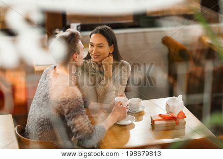 Amorous girl looking at her boyfriend while listening to him in cafe