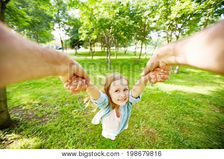 Joyful child being whirled by her parent in park on summer day