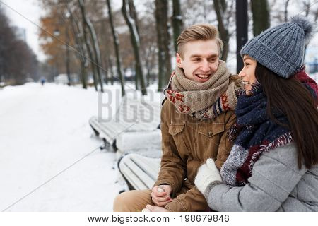 Happy guy talking to his girlfriend while sitting on bench in park on wintery day