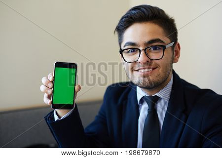 Successful businessman showing curious issue or advert in his smartphone