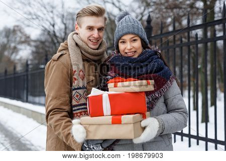 Young couple with xmas presents taking walk on wintery day