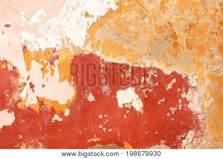Grunge background with old stucco wall texture of beige color and cracked paint of red, pink and yellow color