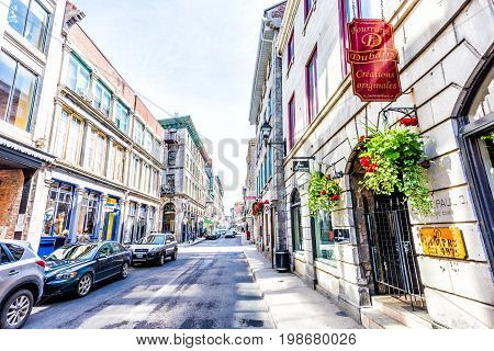Montreal Canada - May 28 2017: Old town area with restaurant sign and red geranium flower pot hanging by street during day outside Fourrures Dubarry in Quebec region city