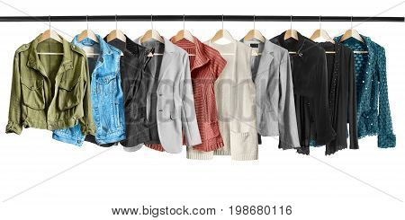 Set of jackets and vests hanging on clothes racks isolated over white