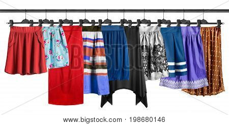 Group of skirt hanging on clothes racks isolated over white