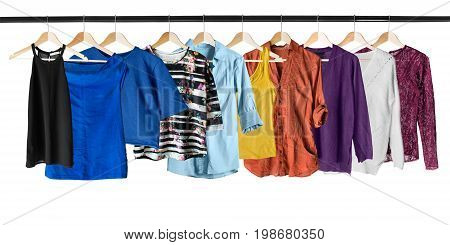 Set of shirts and tops on clothes racks isolated over white
