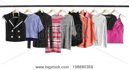 Group of shirts and pullovers on clothes racks on white background