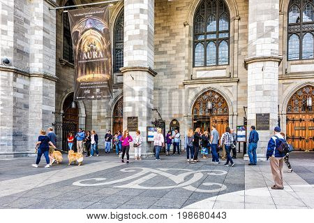 Montreal Canada - May 28 2017: Old town area with Notre Dame Basilica during day and people entering for mass