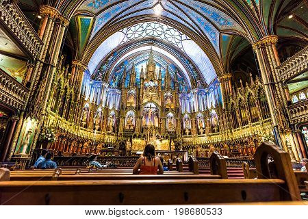 Montreal Canada - May 28 2017: Interior at Notre Dame Basilica during mass people praying inside and detailed altar architecture