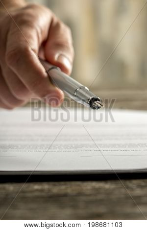 Male Hand Holding Ink Pen Offering You To Sign A Document Or Contract