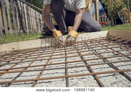 Man making a net of steel bars by clipping them together with a wire and pliers placing it in as a reinforcement in a hole for a concrete foundation outside in backyard retro effect faded look.