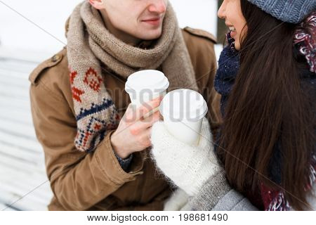 Plastic glasses with hot drinks in hands of amorous couple