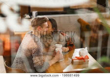 Amorous girl kissing her boyfriend on cheek while having tea in cafe
