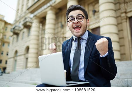 Ecstatic agent with laptop expressing gladness outdoors