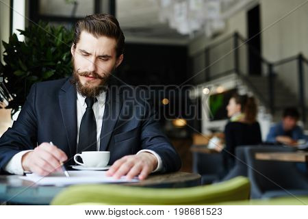 Serious employer reading resumes of applicants in cafe by cup of tea