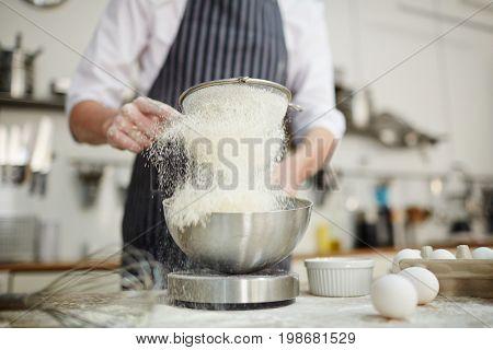 Baker sifting wheaten flour into bowl while preparing dough