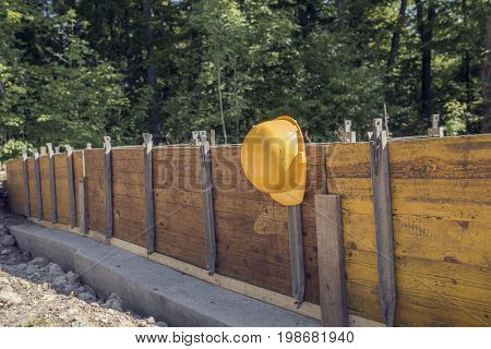 Construction site concept with a yellow hard hat hanging on post of unfinished wall outside in a home garden.