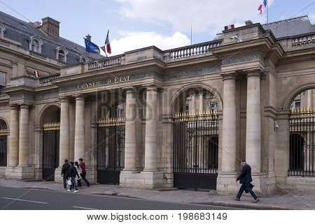 ParisFrance- April 29 2017: The Conseil d Etat (Council of State) is an administrative court of the French government located in the Palais Royal building near the Louvre Museum.Pedestrians walk past