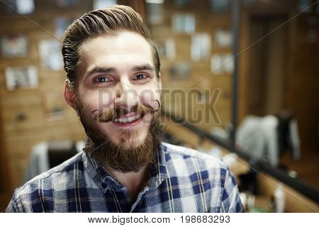 Neat man with beard and moustache looking at camera with toothy smile in haircare salon