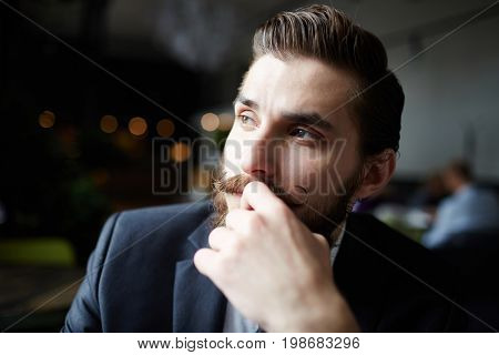 Pensive businessman touching his face while contemplating
