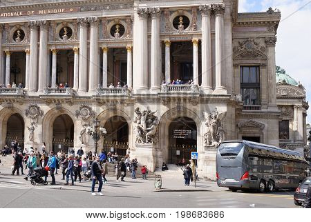 ParisFrance- April 29 2017: View of the Avenue de l Opera with the Palais Garnier opera. On the street pedestrians and moving vehicles