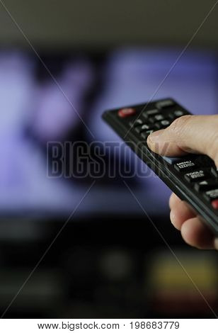 Hand with remote control flicking TV channels