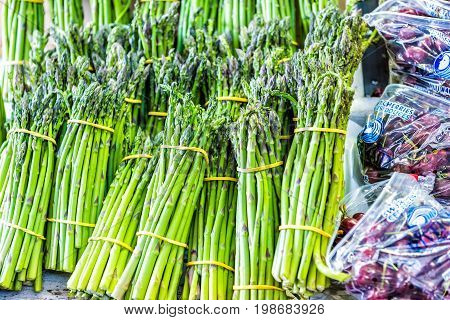 Montreal Canada - May 28 2017: Asparagus and cherries on display at Jean-Talon farmers market during summer