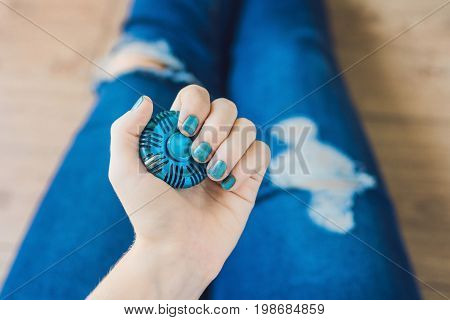 Girl Teenager In Holey Jeans Holds In Hands And Plays With Spinner