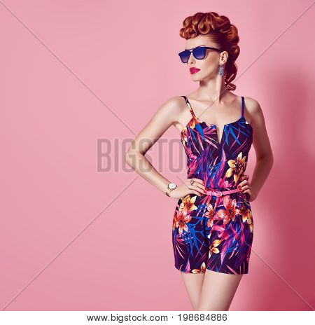 Fashion Redhead Model in Sexy Jumpsuit. Stylish Mohawk hairstyle, fashion Sunglasses, Summer Floral Party Outfit. Beauty Woman in Trendy Summer Dress. Glamour fashion Lady. Playful Luxury Girl on Pink