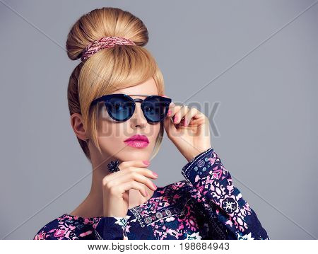 Fashion Model Sexy Girl Portrait. Blond in Glamour Sunglasses, Stylish Hairstyle, Makeup, Trendy fashion Outfit. Cheeky Confident emotion. Beauty Woman in Trendy Luxury fashion Accessories