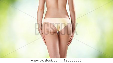 buttocks of woman seen from behind on green blurred background body care concept