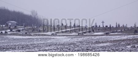 Close up wide landscape of a snow blown cemetery with crosses and headstones near Akwesasne, New York on an overcast blustery day in February.