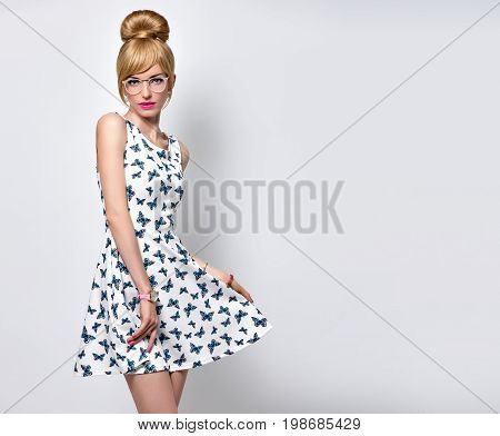Fashion Beauty Sensual Blond Girl in Stylish glasses, Summer Outfit. Stylish Trendy Pinup hairstyle, fashion Makeup, Blue Eyes. Glamour Romantic Model in Butterfly summer Dress