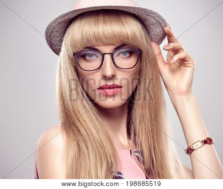 Fashion Portrait Beauty Sensual Blond Model Girl in Stylish glasses. Shiny straight hair, fashion Makeup, Blue Eyes. Trendy Bang Hairstyle. Glamour Sexy Woman in fashion Hat. Luxury summer Accessories