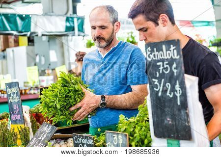 Montreal Canada - May 28 2017: Father and son selling produce by vegetable stands at Jean-Talon farmers market with displays