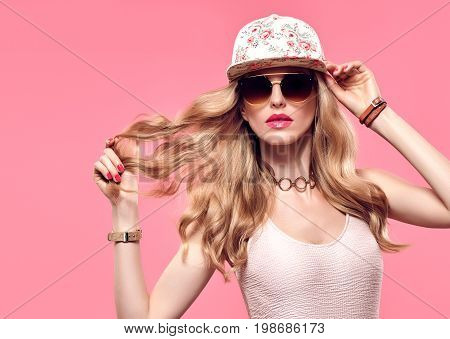 Fashion Model Sexy Girl Portrait. Hipster woman Cheeky emotion. Stylish Summer Outfit. Crazy Blond in Fashion Sunglasses, Trendy fashion Cap. Glamour Wavy Hairstyle. Playful Summer Mood