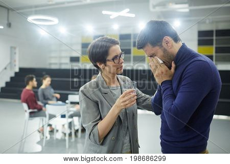Helpful female offering glass of water to crying man