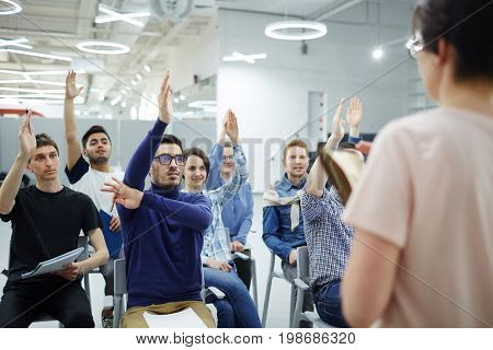 Group of attendants with raised hands looking at their teacher